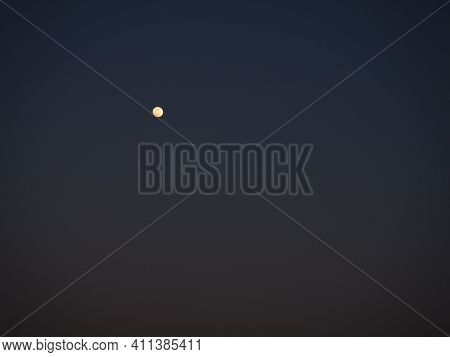 Moon In The Night Dark Blue Sky. White Point In The Sky. Dark Vignetting Around The Edges Of The Ima