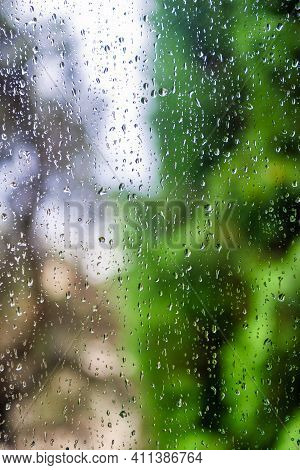 Water Drops On Window Glass With Blur Garden Background