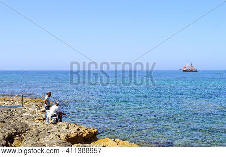 Paphos Harbour, Cyprus, Greece - June 8, 2018 : Two Men Fishing In Paphos Harbour A Popular Tourist