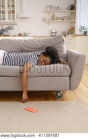 Tired African American Young Woman Wear Stripped T-shirt Sleeping On Couch At Home, Cellphone On The