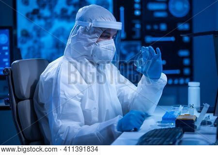 Doctor in protective suit is doing a science experiments and developing vaccine in a modern laboratory. Genetic engineers workplace. The concept of science and medicine.