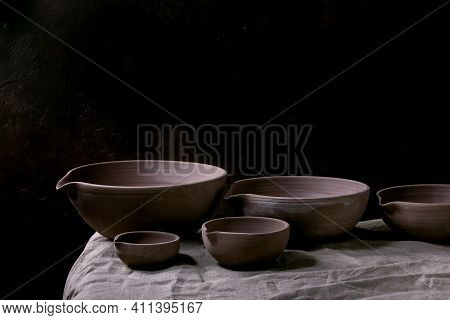 Set Of Craft Handmade Unglazed Dark Clay Pottery Bowls With Spout On Table With Dark Background.