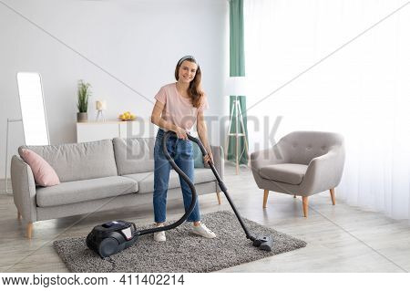 Happy Young Housemaid Tidying Her Flat, Vacuuming Rug, Indoors. Cheerful Millennial Lady Doing House