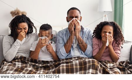 Portrait Of Sick Young Black Family Of Four People Blowing Runny Noses While Sitting Together On The
