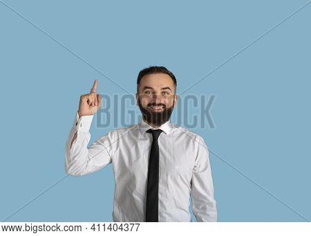 Happy Millennial Businessman In Formalwear Pointing Upwards At Empty Space On Blue Studio Background