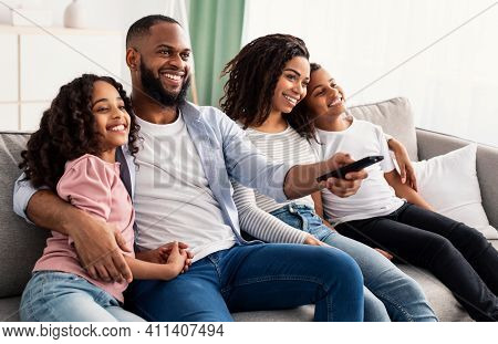 Comfort And Relax. Portrait Of Happy Loving Black Family Of Four People Watching Tv, Smiling Parents