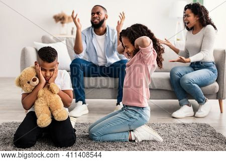 Family Conflicts. Sad Little Black Children Covering Ears With Hands While Their Parents Arguing In