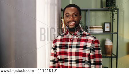 Portrait Of Handsome Young Joyful African American Man In Good Mood Standing In Room Near Window Smi