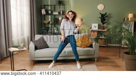 Happy Joyful Young Caucasian Beautiful Woman In Positive Mood Dancing Moving Rhythmically And Jumpin
