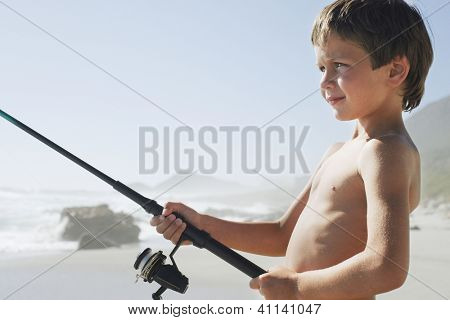 Side view of shirtless preadolescent boy standing with fishing rod