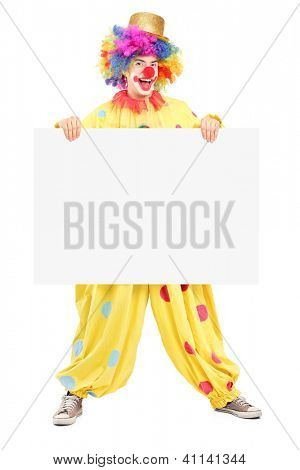 Full length portrait of a male clown with happy joyful expression holding a blank panel isolated on white background