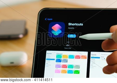 Apple Shortcuts Logo Shown By Apple Pencil On The Ipad Pro Tablet Screen. Man Using Application On T