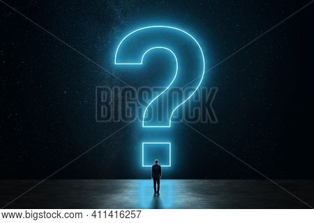 A Business Man In A Suit Standing In Front Of A Huge Question Mark. The Concept Of Solving A Problem