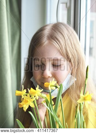 Coronavirus Is Over. Little Girl Sitting On The Windowsill And Removing Face Medical Mask, Sniffing
