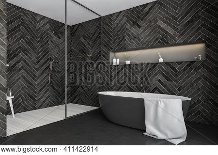 Dark Bathroom With Bathtub On Grey Tiled Floor And Light Wooden Rug In Shower With Glass Partition,