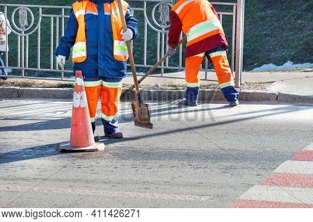 Wipers In Bright Orange Reflective Uniforms Sweep The Street And Remove Debris From The Driveway And