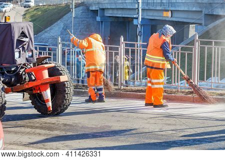 Female Street Sweepers In Bright Orange Uniforms Sweep The Road After The Melted Snow On The Drivewa