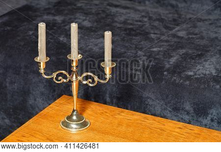 A Gilded Glittering Candlestick With Three White Unlit Candles Stands On An Oak Wood Tabletop Agains