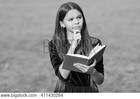 Think Clearly And Rationally. Serious Child Think Holding Book Green Grass. Critical And Creative Th