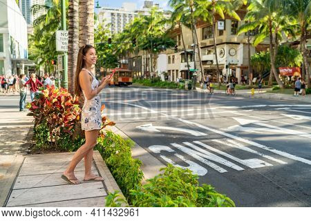 Waikiki tourist woman walking in Honolulu city street using mobile phone. Hawaii Summer vacation destination.