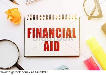 Text Financial Aid In Notebook On White Table With Office Tools.