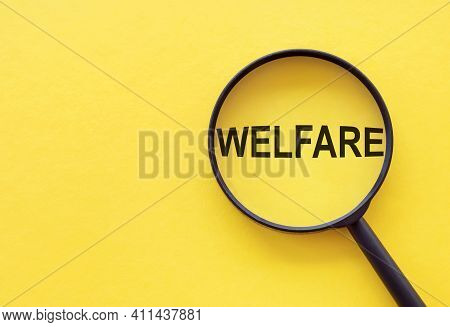 The Word Welfare Is Written On A Magnifying Glass On A Yellow Background.