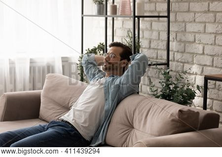 Peaceful Young Man Recline On Sofa Breath Deep Enjoy Nap