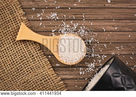 Desiccated Coconut Flakes On Small Wooden Spoon