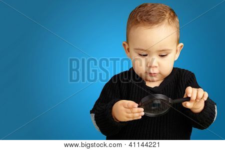 Baby Boy looking at Magnifying Glass against a blue background