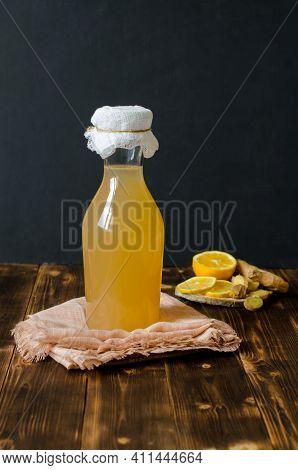 Homemade Kombucha Is A Fermented, Probiotic, Organic Beverage, Or Ginger-lemon Ale. Rustic Dark Wood