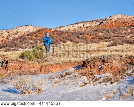 senior male is hiking with trekking poles at Colorado foothills of Rocky Mountains - Red Mountain Open Space, a popular hiking, biking and horse riding area near Fort Collins