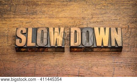 slow down word abstract in vintage letterpress wood type against rustic wooden background, work, stress and lifestyle concept