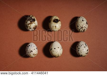 Creative Quail Egg Layout On Brown Background. Quail Eggs Pattern. Happy Easter Concept. Minimal Des