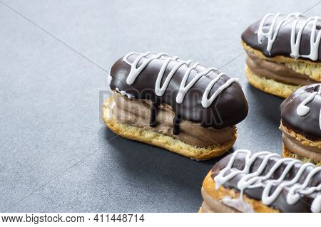 Eclairs With Black Chocolate And White Chocolate With Custard On Rustic Table. Traditional French De
