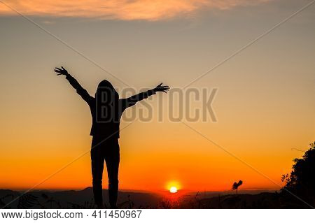 Silhouette Of A Woman With Hands Raised In The Sunset Concept For Religion, Worship, Prayer And Prai