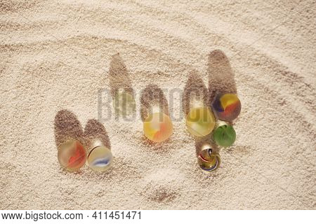 sea glass marbles on white sand beach with corall shadow