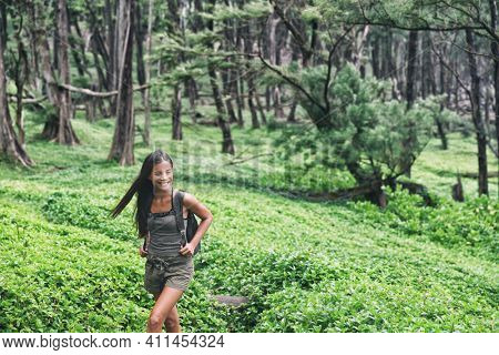 Happy hiker backpacking walking in forest. Hiking Asian woman trekking on trail trek with backpack living healthy active lifestyle. Girl on Hawaii hike in mountain nature landscape.