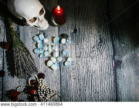 Wooden Table With Occult Attributes. Rune Stones, Candles, Dry Lavender, Skull, Rosaries