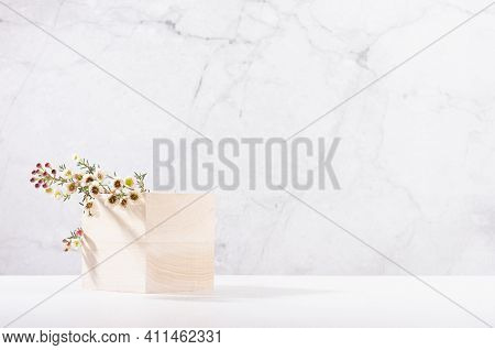 Wooden Cube Podium With Twig Of White Spring Flowers In White And Grey Marble Interior With Sun Ligh
