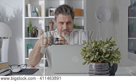 Older man working online with laptop computer at home sitting at desk. Home office, browsing internet, study room.