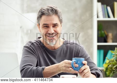 Portrait of happy man at home sitting at desk, drinking coffee, looking at camera. Happy smile, grey hair, beard. Portrait of mature age, middle age, mid adult man in 50s.