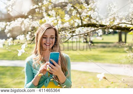 Young woman using her phone on a beautiful day in spring standing amid blossoming tree