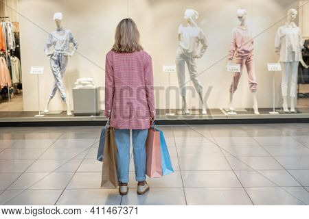 Rear view of young woman holding shopping bags and looking at shop window in the mall
