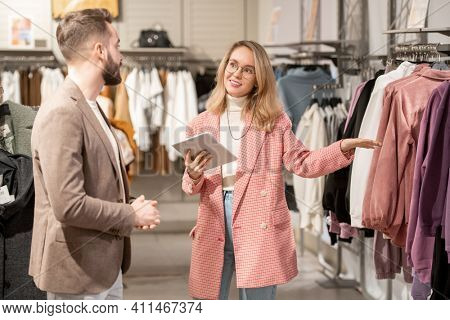 Young shop assistant using digital tablet and consulting customer in the clothing shop