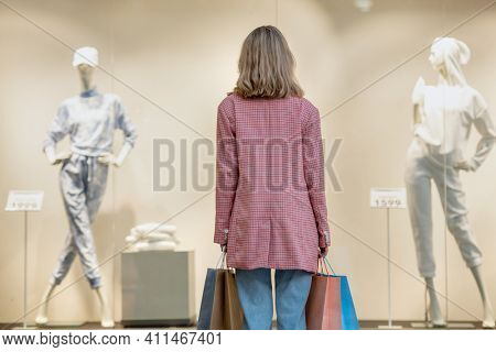 Rear view of shopaholic with shopping bags looking at shop window in the mall