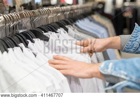 Close-up of woman choosing white shirt for herself in the clothing shop in the mall