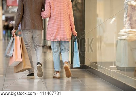 Rear view of young couple with shopping bags walking along the shopping mall