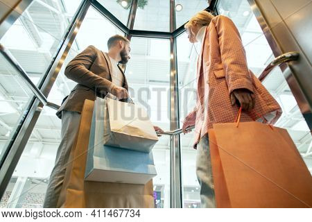 Young people with shopping bags standing in elevator while doing shopping in modern shopping mall