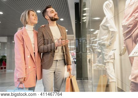 Young couple looking at mannequin in suit behind the shop window during their shopping in the mall