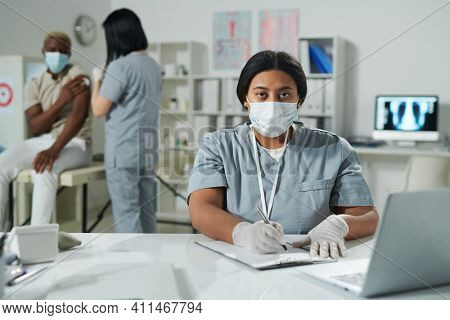 Young mixed-race clinician in protective workwear filling in medical document by desk while her colleague vaccinating African male patient
